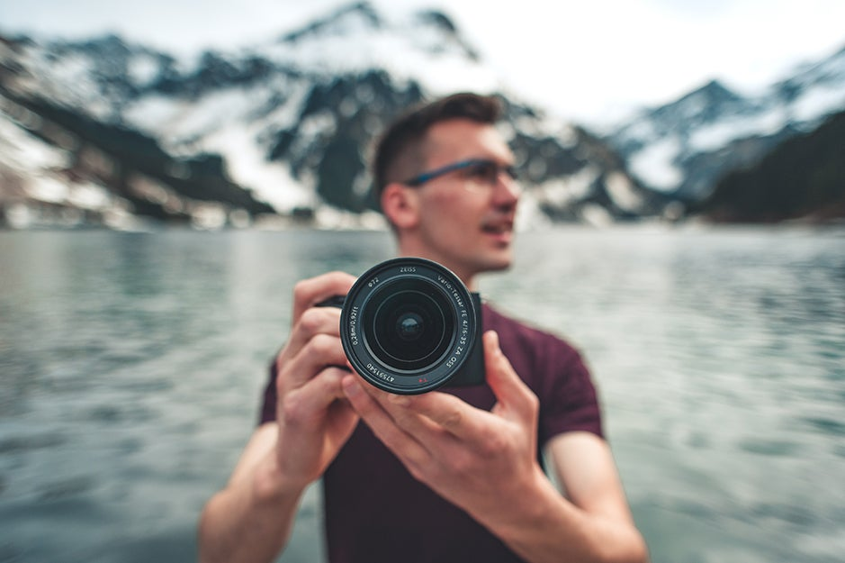 person with a camera in front of a lake