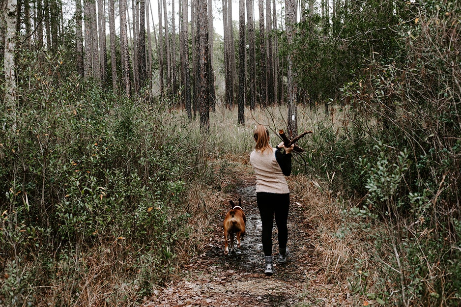 woman walking with dog in the woods