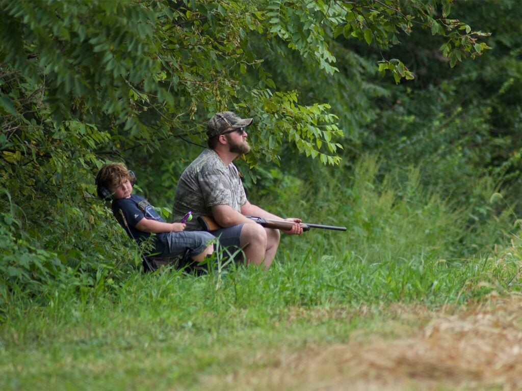 A man and son hunting doves in a field.