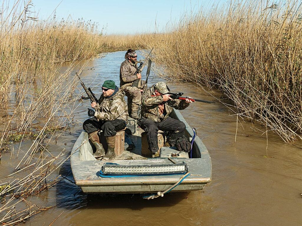 Hunters on a boat in a swamp.