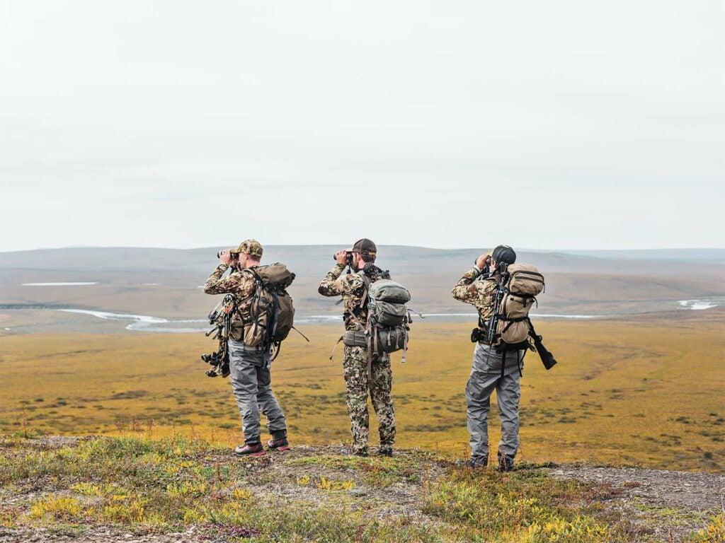 Hunters using binoculars to scout a field.