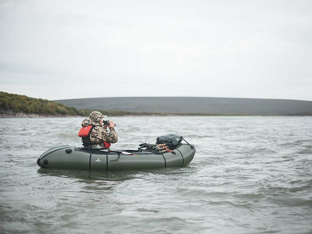 Hunter in a packraft scouting a riverbank.