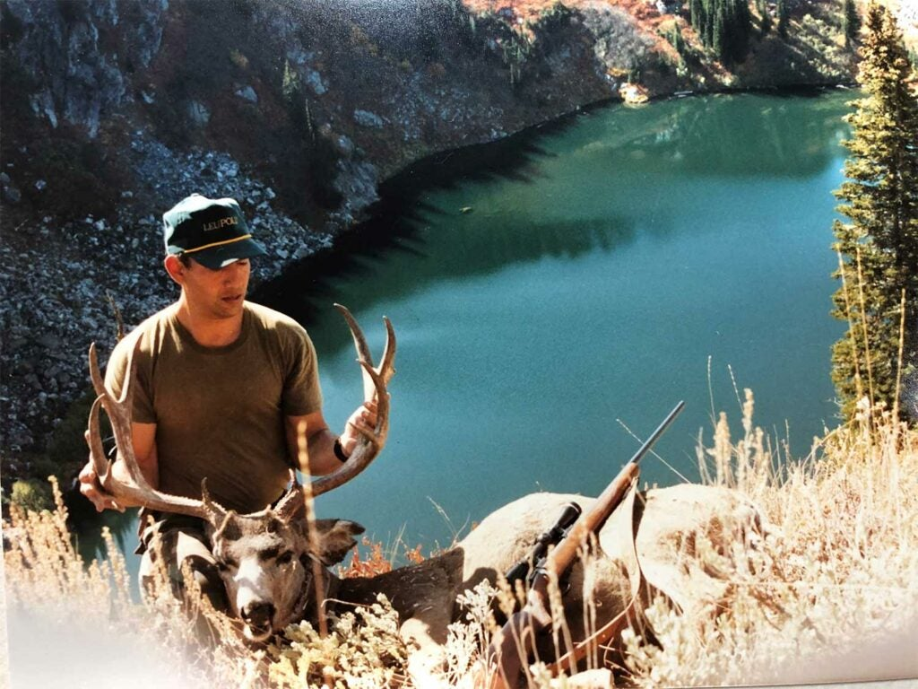 man posing with a large deer.