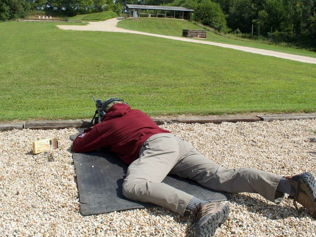 Man lying prostrate on the ground while aiming a rifle.