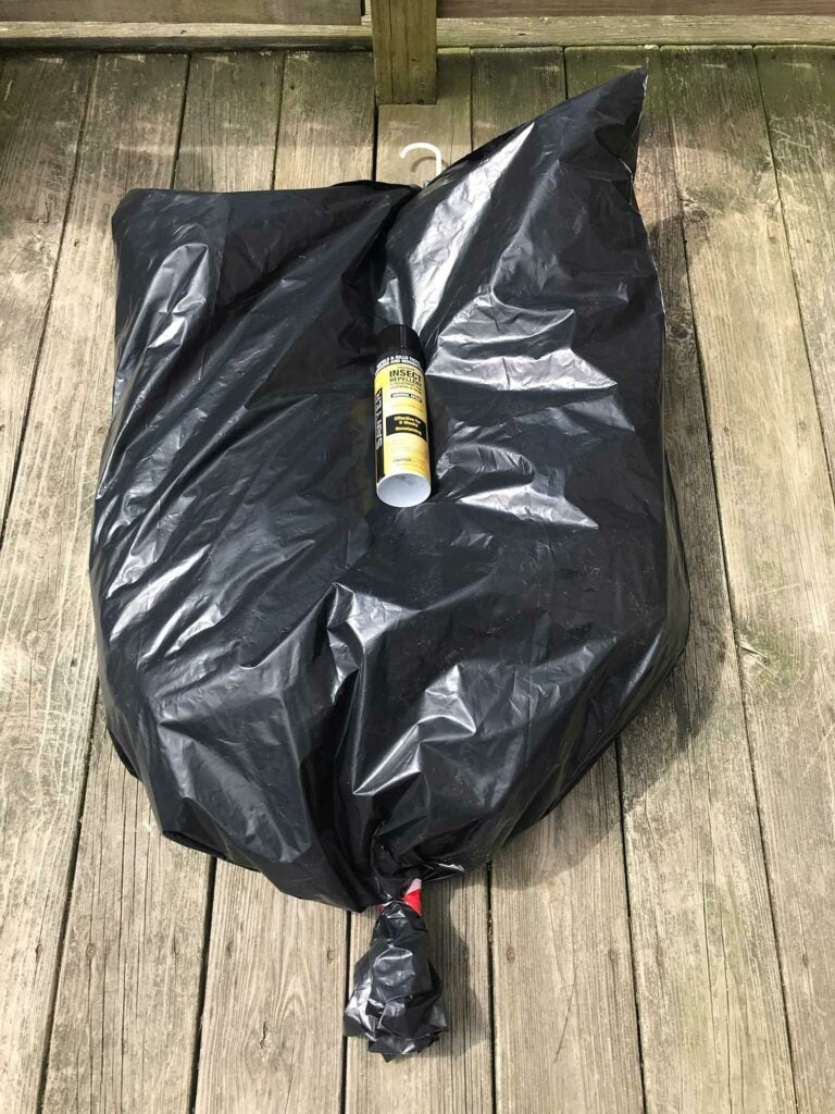 A bag with a can of permethrin.
