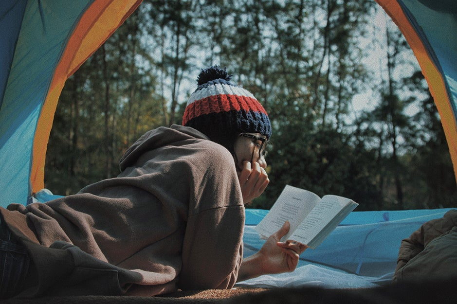 person reading in a tent