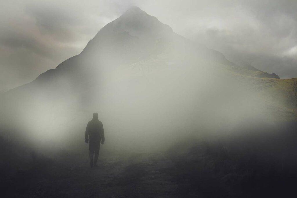 Hiker in a dense fog near a mountain.