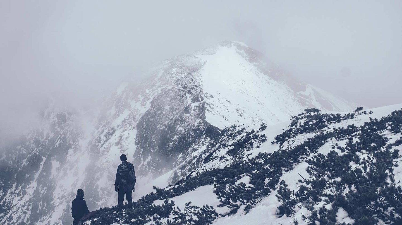 Hiker climbing a snowy mountain.