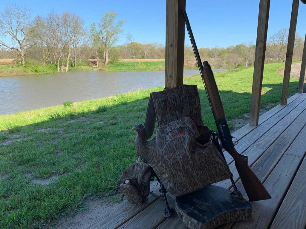 Hunting gear and rifles on a cabin porch.
