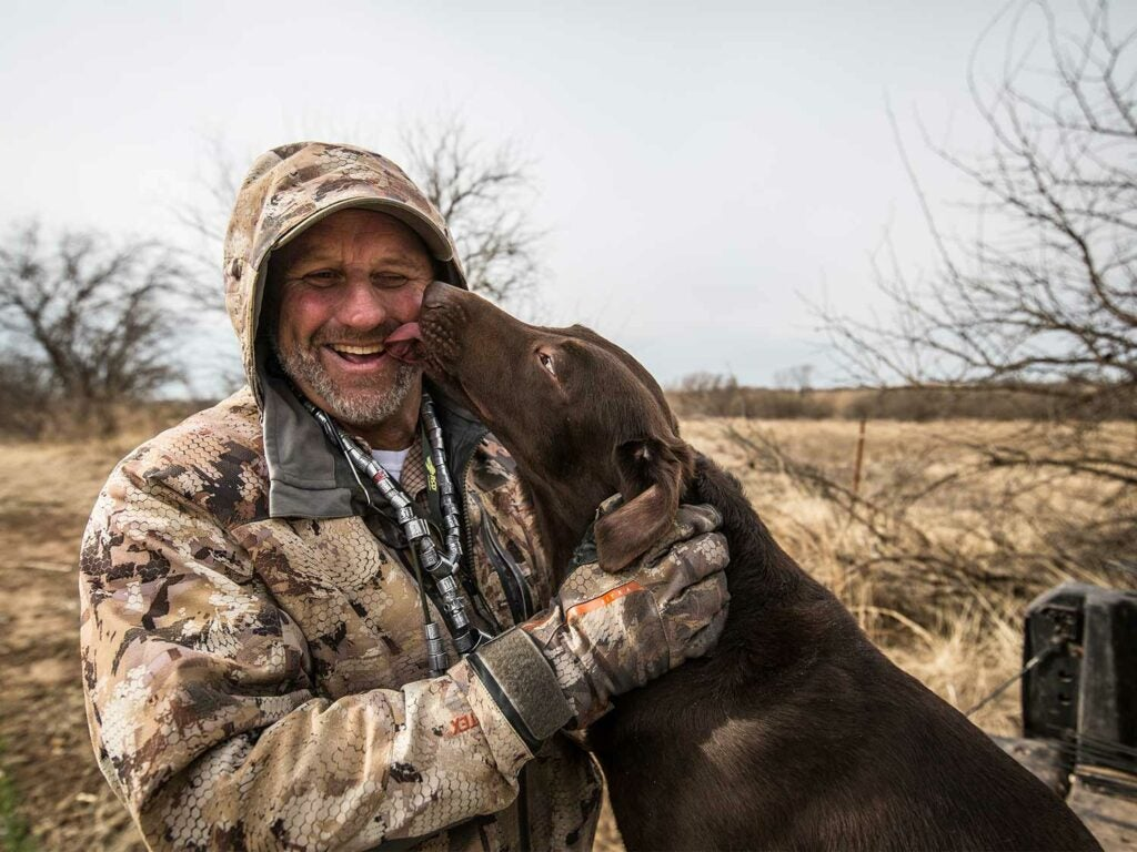 A man and a chocolate lab in a field.