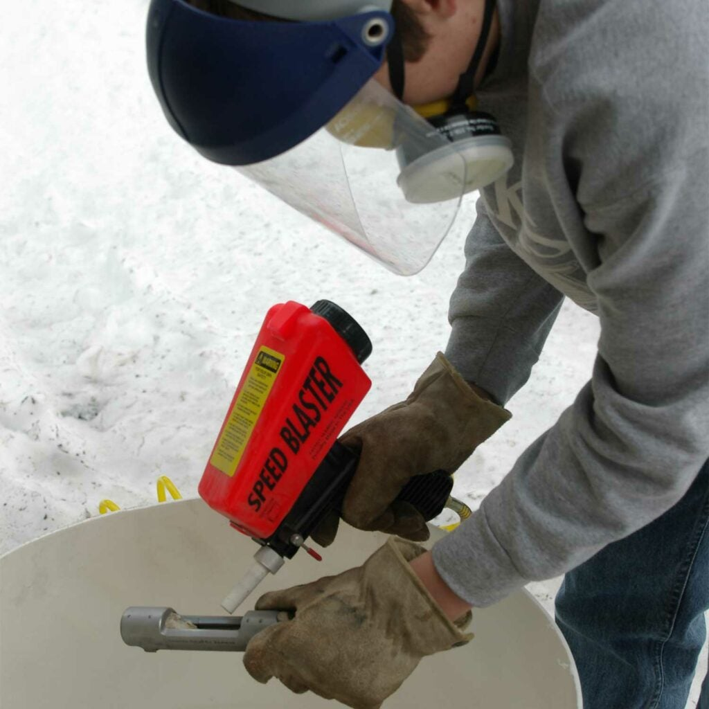 A man using small gravity feed sandblaster to sand a gun.
