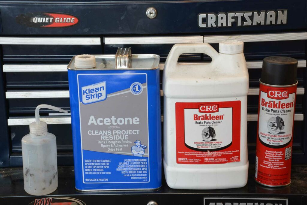 Two containers of Acetone and Brakleen.