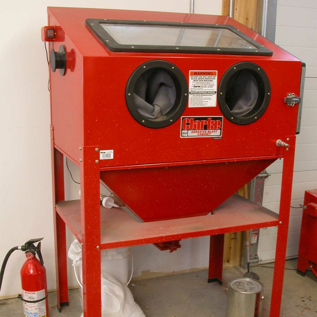 A large red sandblasting cabinet.