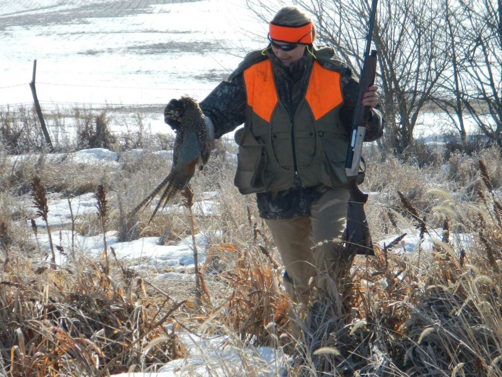 A hunter carrying a pheasant through the snow.