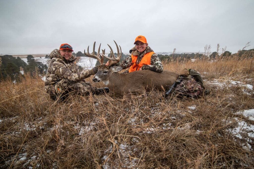 Two hunters with a mule deer in the snow and grass.