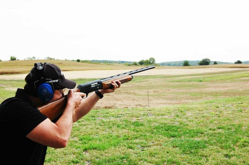 A man aiming a shotgun in an open field.