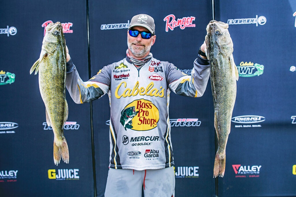 Brian Bashore holds up two walleye at a fishing tournament.