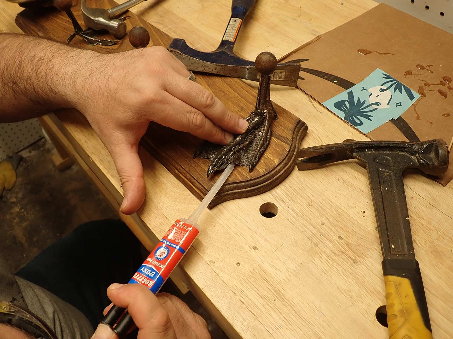 Attaching duck feet to a wall  plaque with epoxy.