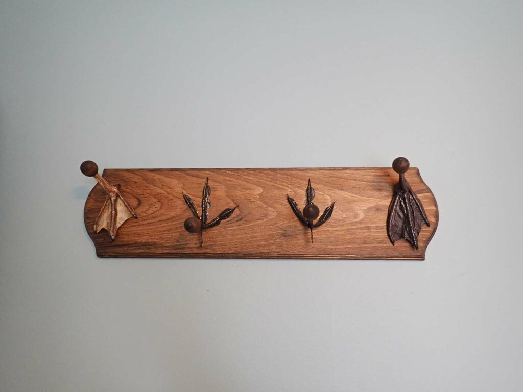A hat rack made of wood and duck feet.