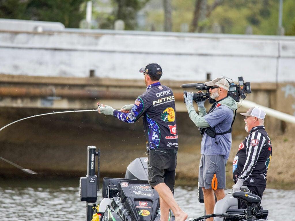 Angler Ott Defoe fishing while a camera crew films.