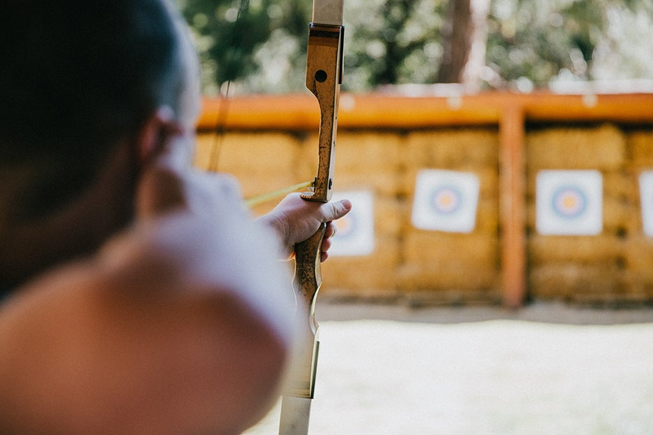 person aiming at archery target