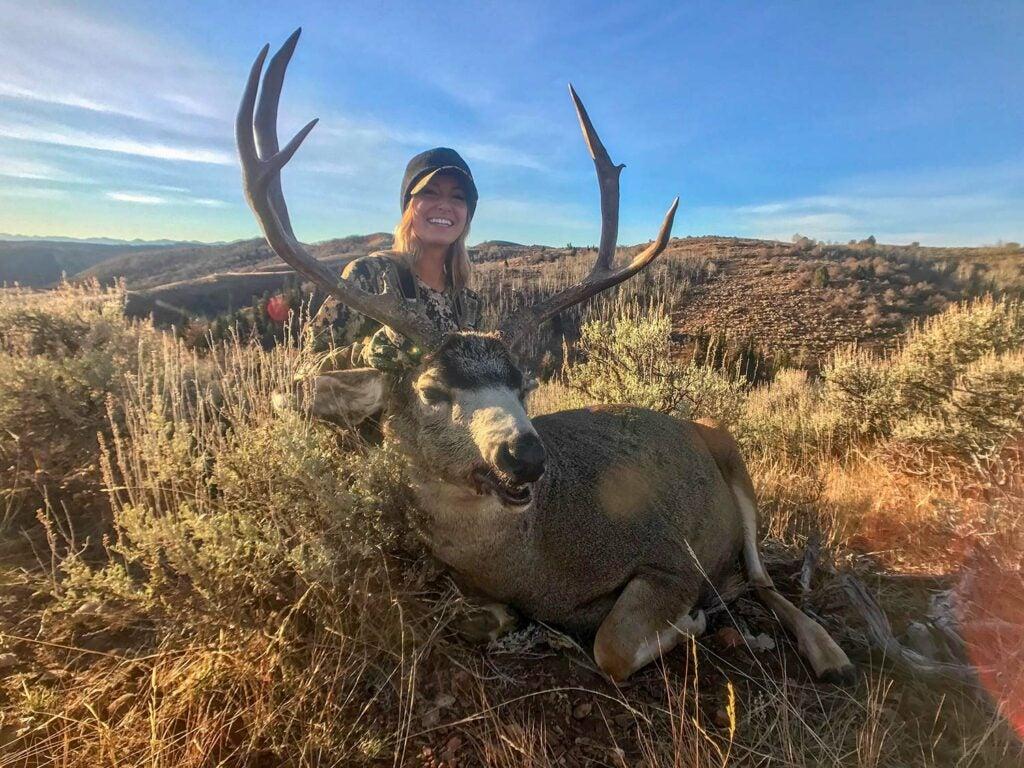 A female hunter kneeling behind a giant large mule deer.