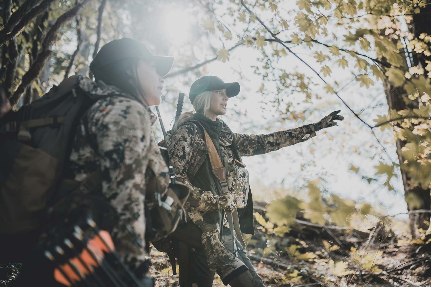 Two female hunters on a trail through the woods.