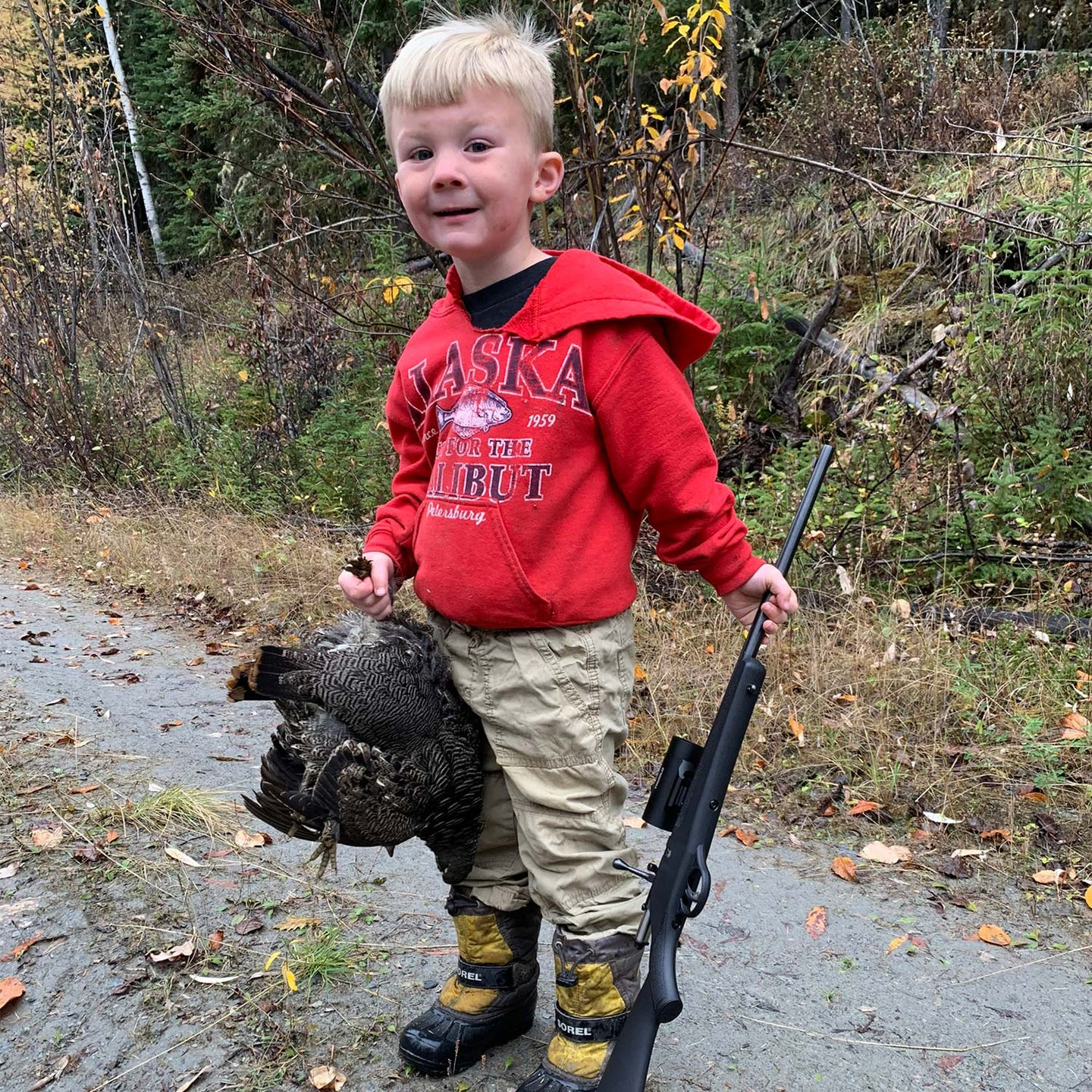 A young child holding up a spruce grouse.