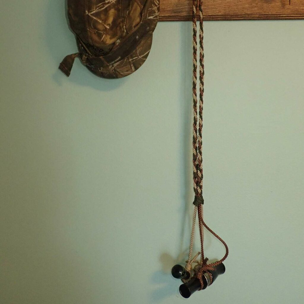 A duck call hanging from a lanyard.