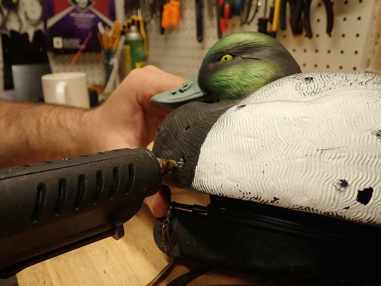 Applying hot glue to a waterfowl decoy.