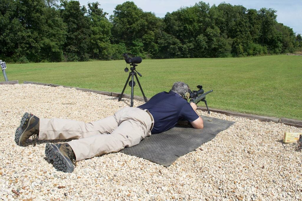 A man laying prostrate on the ground while aiming a rifle using bipods.