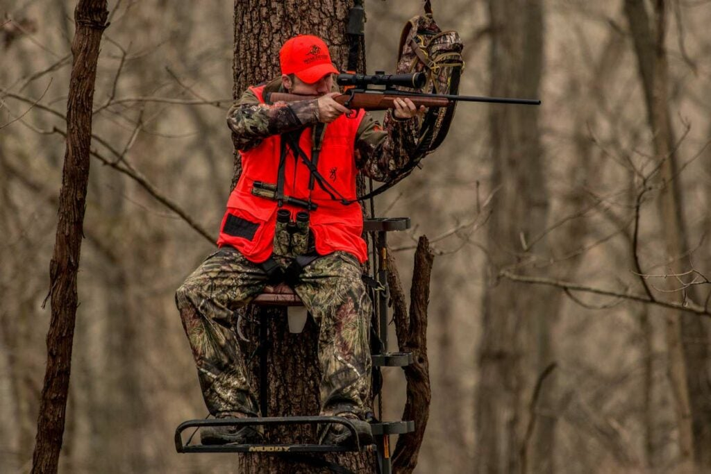 A hunter in an orange vest and hat fires a rifle from a treestand.