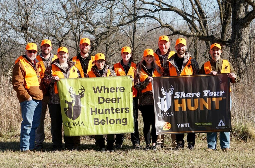 A group of hunters in orange holding up promotional signage.