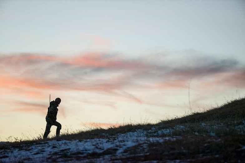 A single hunter hikes up a snowy hillside in the morning light.