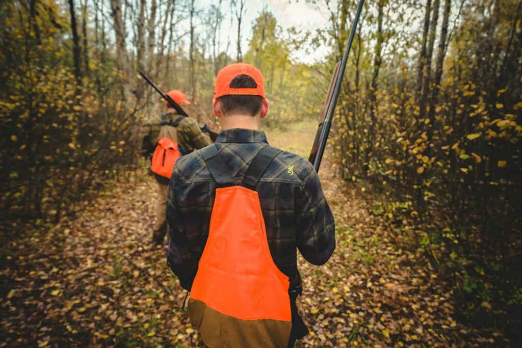 A hunter in orange walking through a trail in the woods.