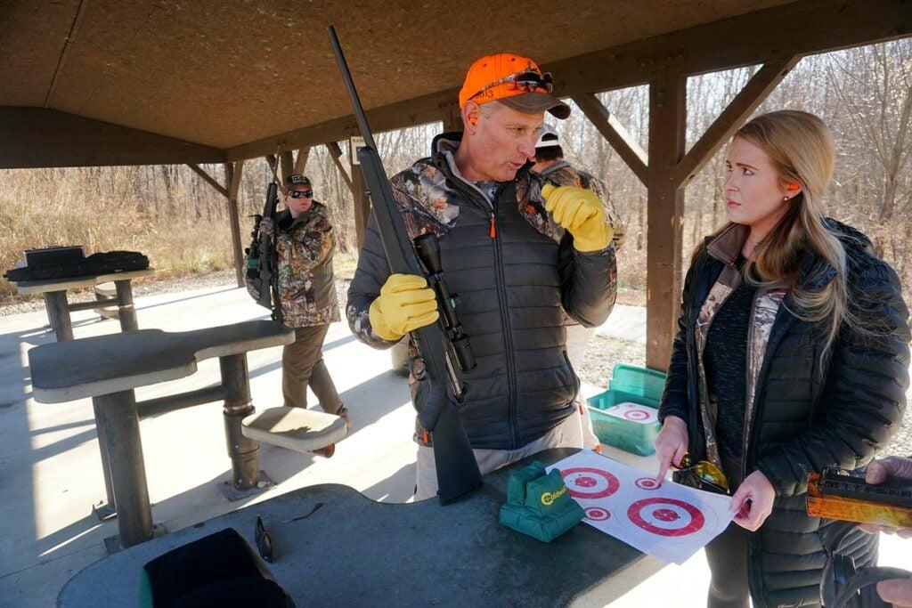 A hunter mentoring another hunter at a shooting range.