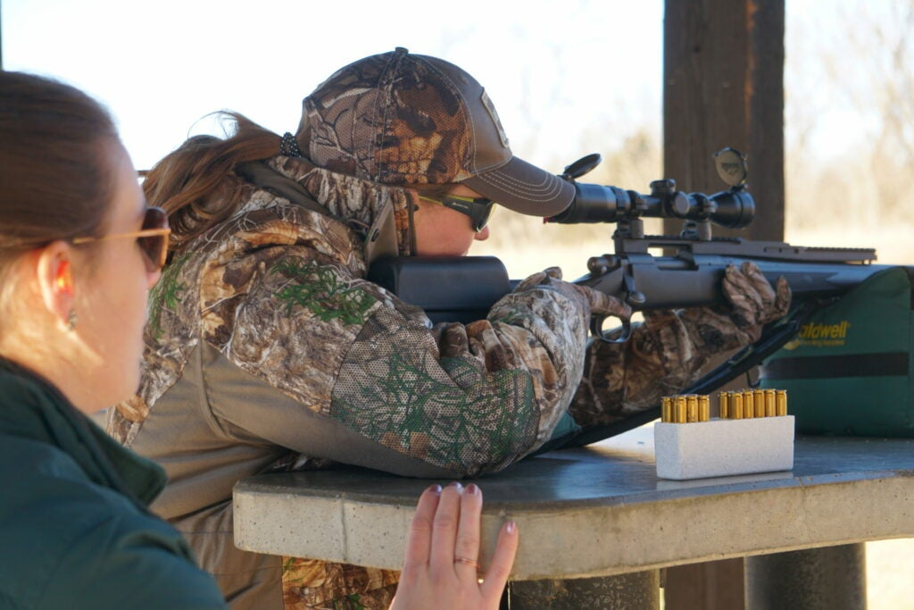 Deer hunter sights in her hunting rifle at the shooting range while an instructor watches.