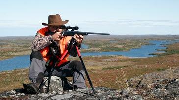 Hunter aiming a rifle using a bipod.