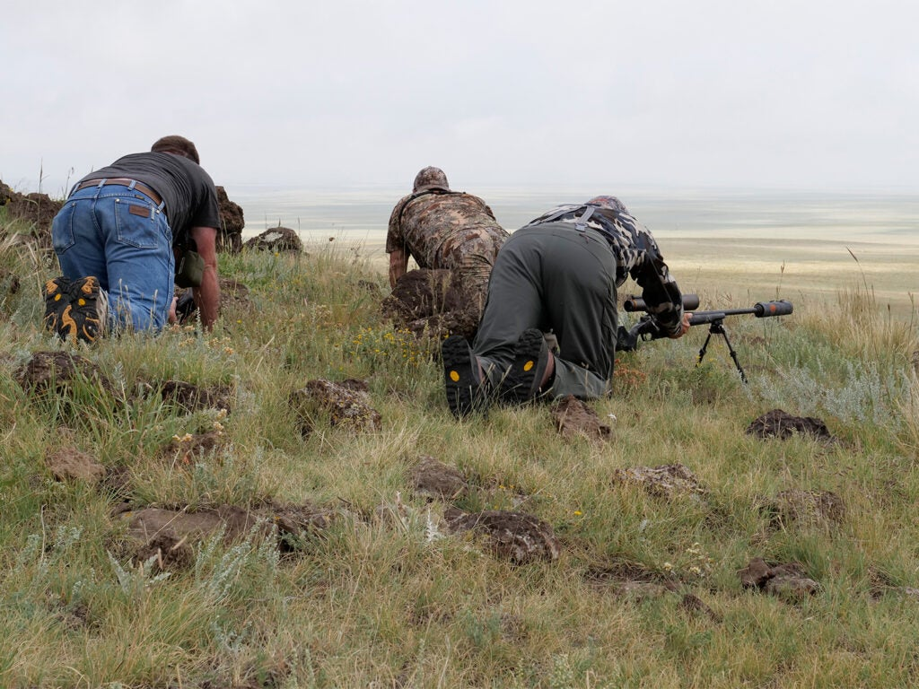 Hunters setting up rifle shooting spots on a hillside.