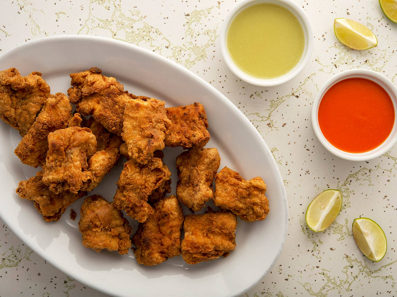 Nuggets of fried bass served with lemon and sauces.