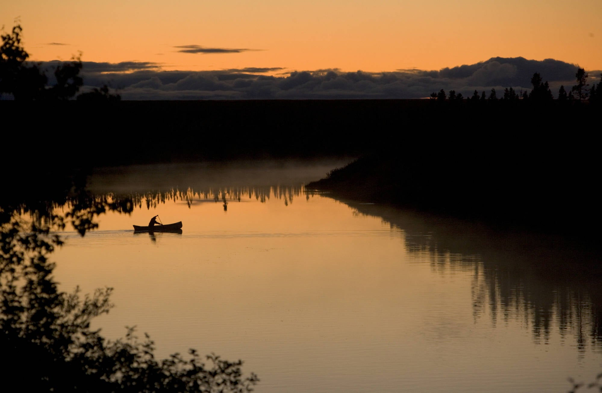 Silhouette of a paddler canoeing across a calm lake at sunrise or sunset