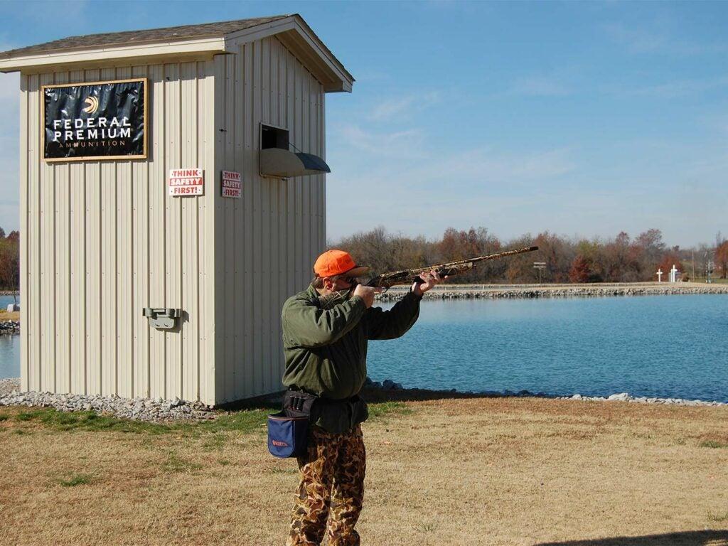 A man shooting skeet in a field.