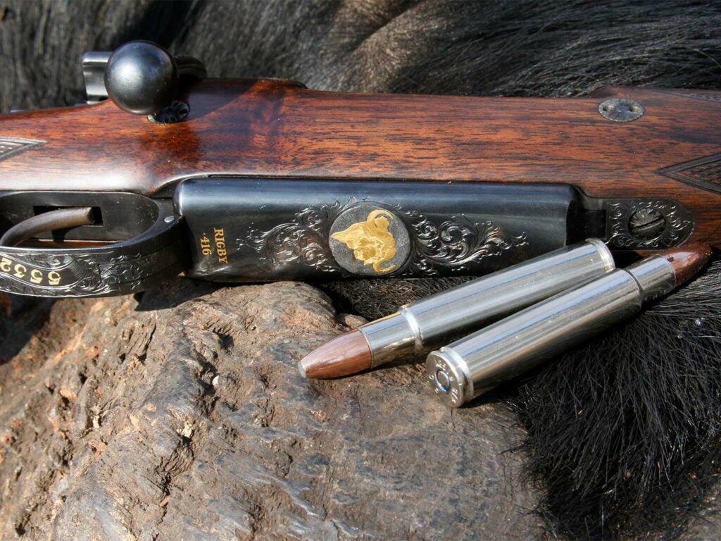 A hunting rifle and and hunting ammo cartridges on a rock.