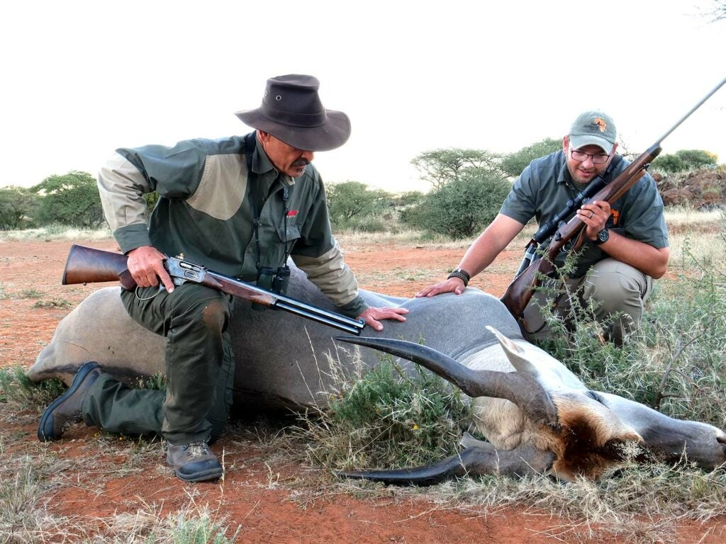 Two male hunters kneeling next to a downed pronghorn while holding rifles.