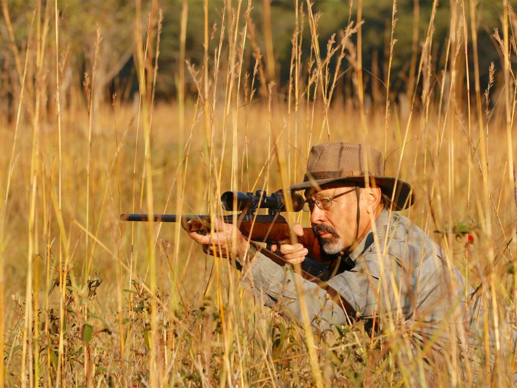 A hunter aiming a rifle in a large field while on an African Safari.