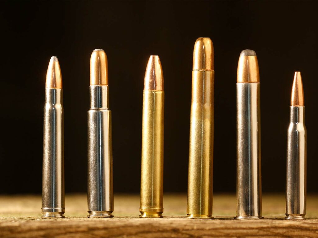 A lineup of six rifle ammo cartridges standing on a table.