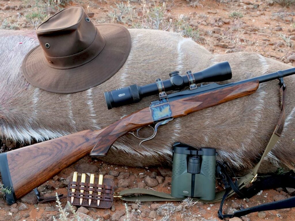 A setup of hunting rifles, ammo, and hunting gear next to down big game.