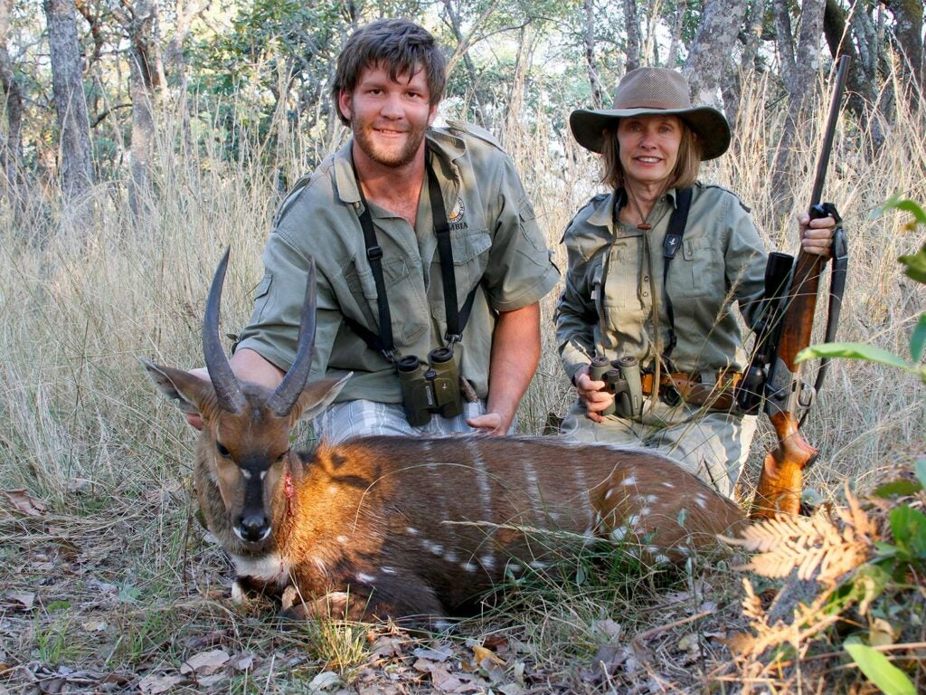 A male and female hunter kneels behind a bushbuck ram.