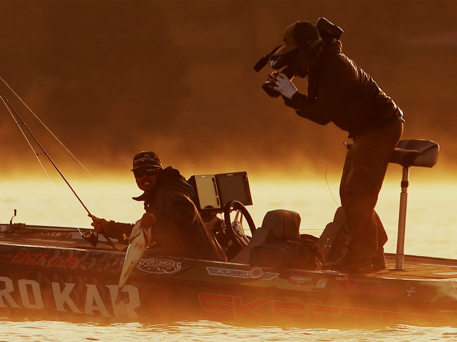 A bass angler pulling a fish into a boat while a camera man films.