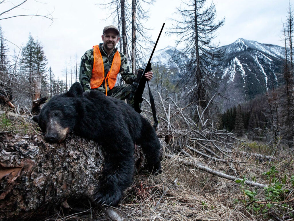 A hunter with a large black bear in the forest.